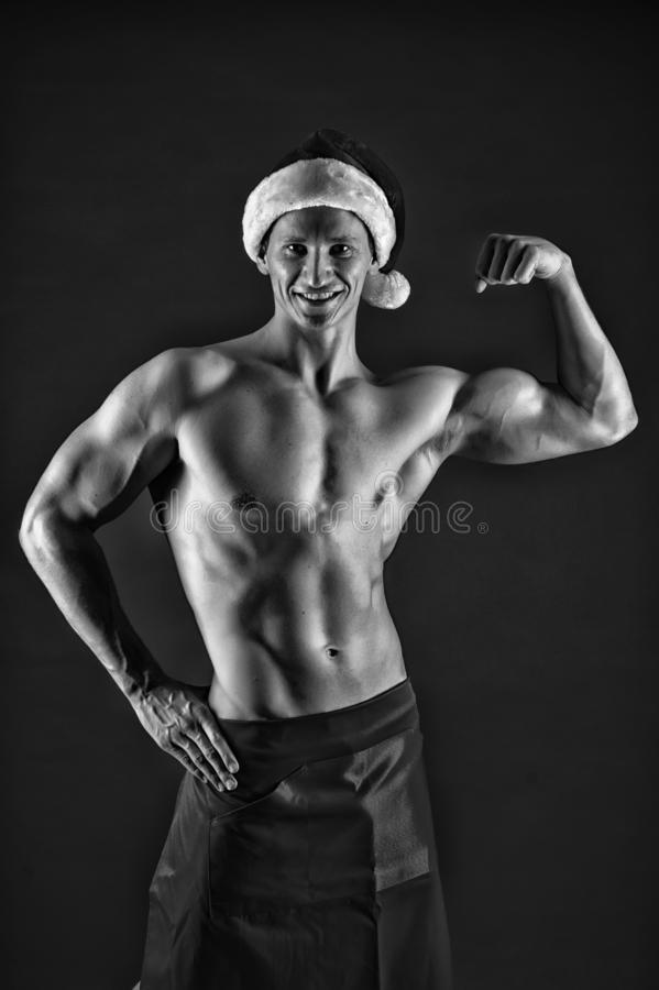Macho sexy muscular torso posing confidently. Santa claus comes not only to good girls. Athlete man wear santa hat and royalty free stock photos