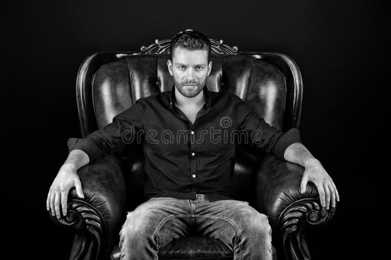 Macho sitt i läderfåtölj på mörk bakgrund royaltyfri foto