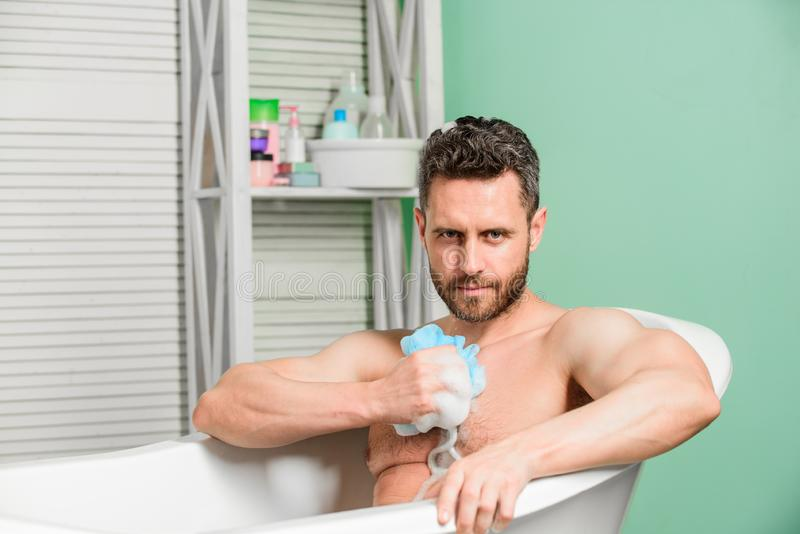 Macho sitting naked in bathtub washing with sponge. hygiene and health. Morning shower. desire and temptation. personal royalty free stock photos