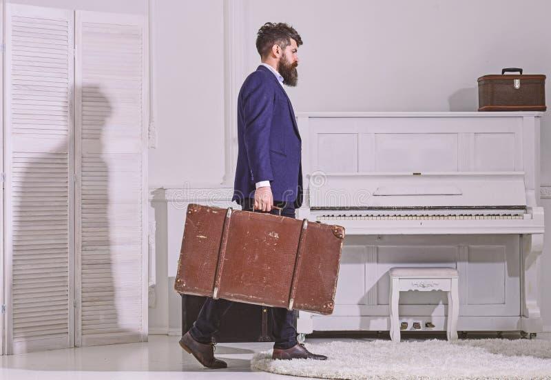 Macho stilfullt på strikt framsida går och bär den stora tappningresväskan, sidosikt Bagage och resande begrepp man royaltyfria foton