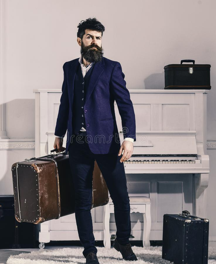 Macho stylish on strict face stands and carries big vintage suitcase. Baggage and travelling concept. Man, traveller royalty free stock photography