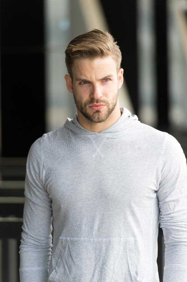 Macho in sweatshirt outdoor. Bearded man with serious face on fresh air. Taking a minute break. Casual in style. Sporty. Handsome stock image