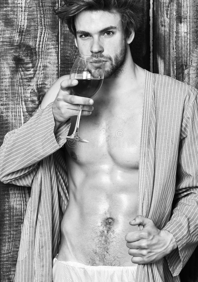 Macho tousled hair degustate luxury wine. Drink wine and relax. Guy attractive relaxing with alcohol drink. Man sexy. Chest wet skin after bath hold wineglass royalty free stock photography
