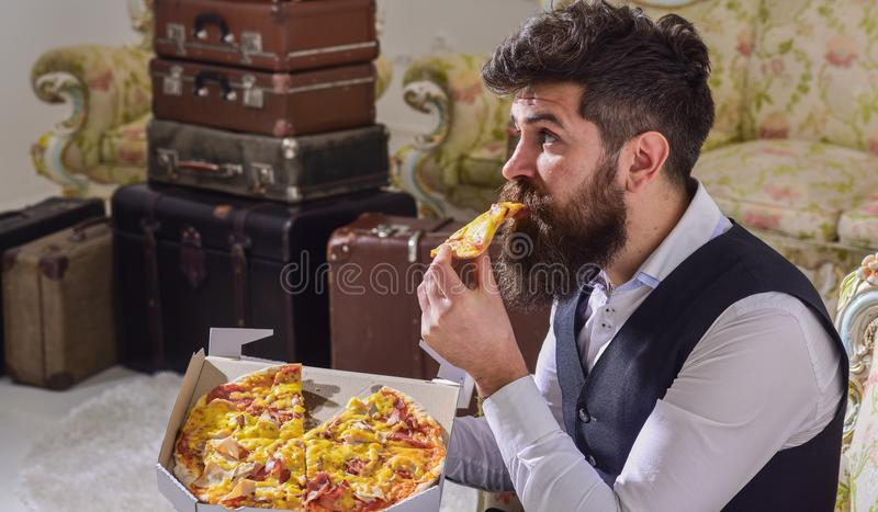 Macho in vestiti classici affamati, sul fronte sorpreso, la fetta dei morsi di pizza, mangia, fondo interno Uomo con la barba e fotografie stock