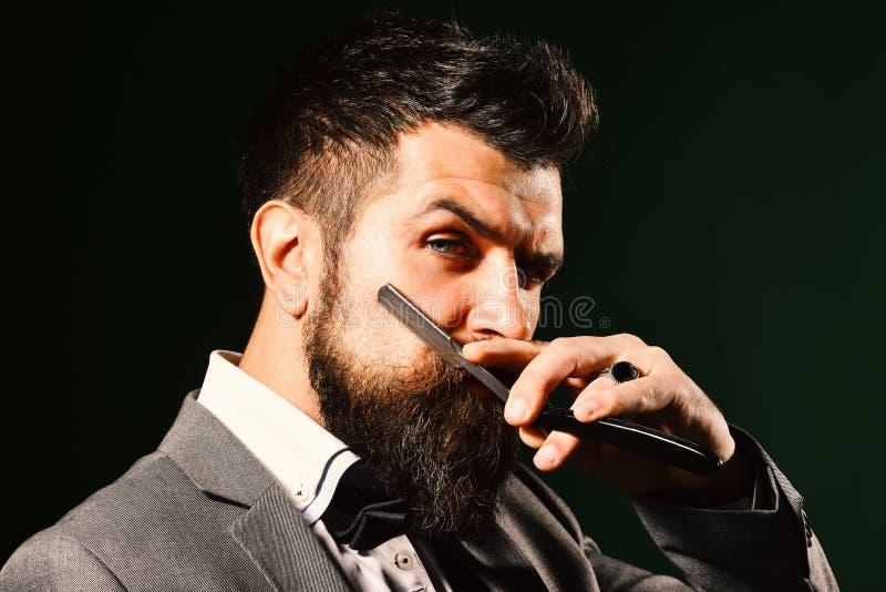 Macho in vestito convenzionale rade la barba Pubblicità del parrucchiere fotografia stock