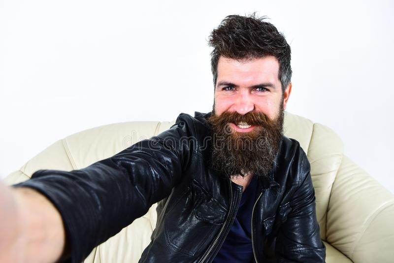Macho wears leather jacket, white background. Man with beard and mustache on smiling face looking at camera. Hipster royalty free stock photo