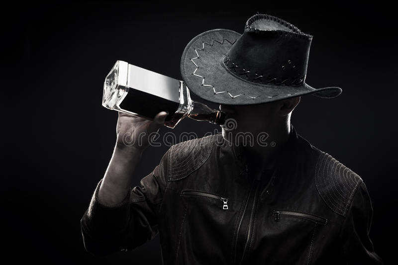 Macho with whisky. Brutal macho in hat drinking whisky over dark background royalty free stock photos