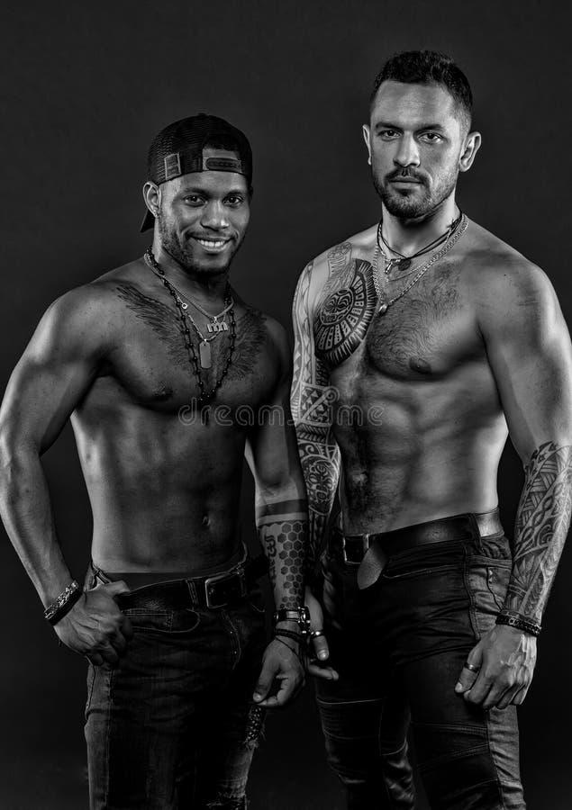 Machos z mięśniowymi tatuować półpostaciami patrzeją atrakcyjnym, ciemnym tłem, Facetów sportowowie z seksownymi mięśniowymi półp fotografia stock