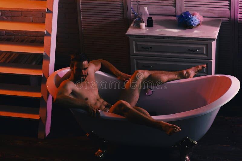 Machozitting naakt in badkuip als erotica en geslachtsconcept stock foto