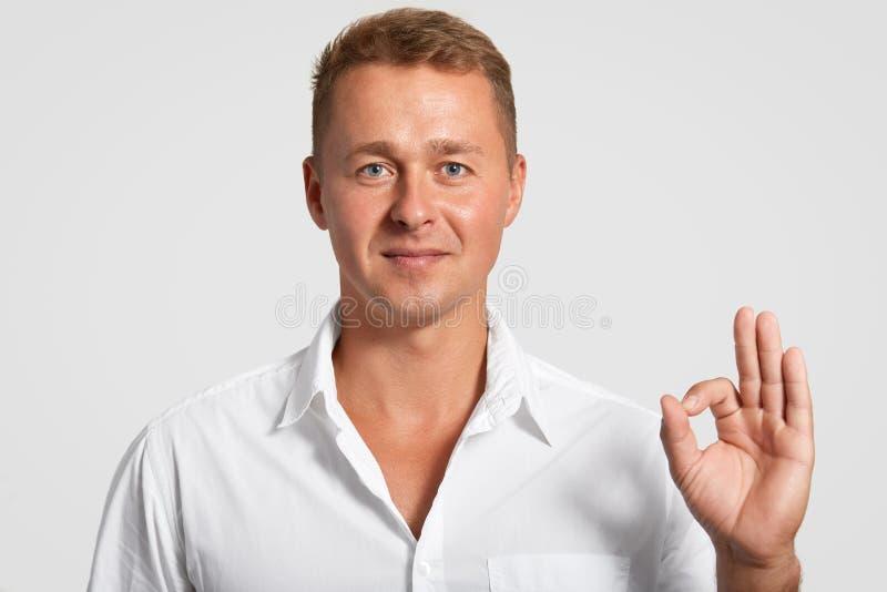 Macht erfüllter Selbst sicherer gutaussehender Mann mit überzeugtem Ausdruck, okaygeste, zeigt seine Vereinbarung mit etwas, here lizenzfreies stockfoto