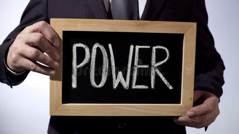 Macht op bord, het teken van de zakenmanholding, zaken, politiek wordt geschreven die stock foto's
