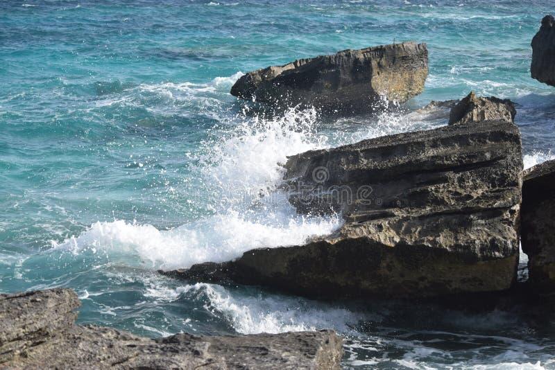 Macht van de oceaan die op sommige rotsen verpletteren stock foto's