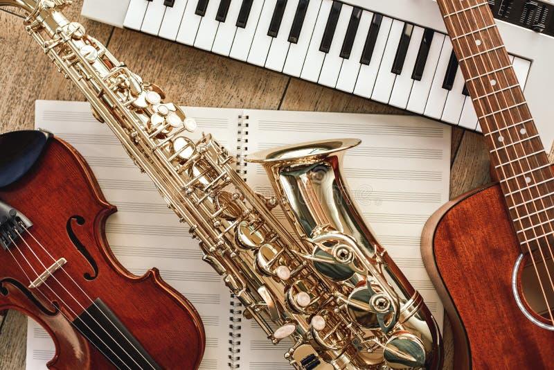Macht van muziek De hoogste mening van muzikale instrumenten plaatste: synthesizer, gitaar, saxofoon en viool die op de bladen li stock foto's