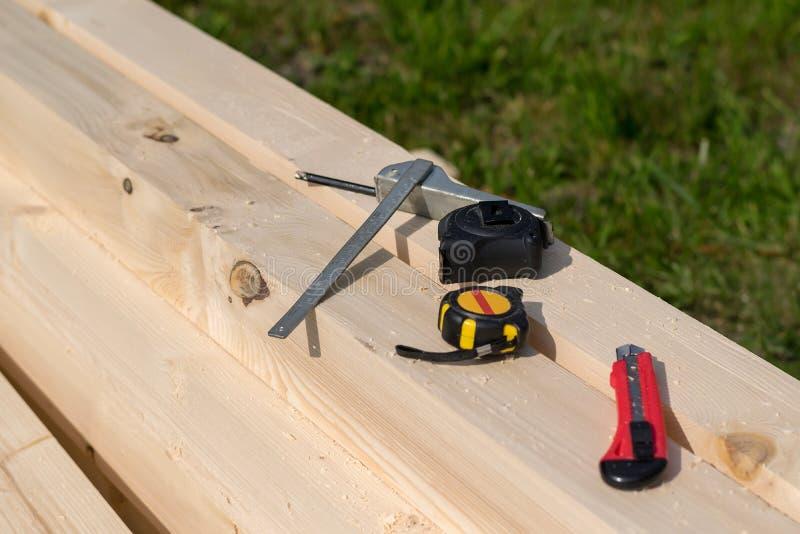Machthaber, Maßband und Messer liegen auf dem Bauholz mit Sägemehl stockfoto