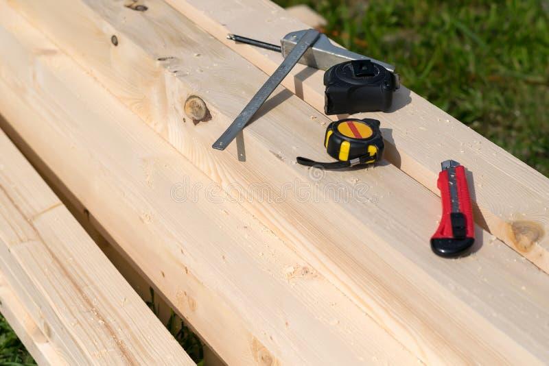 Machthaber, Maßband und Messer liegen auf dem Bauholz mit Sägemehl stockbild