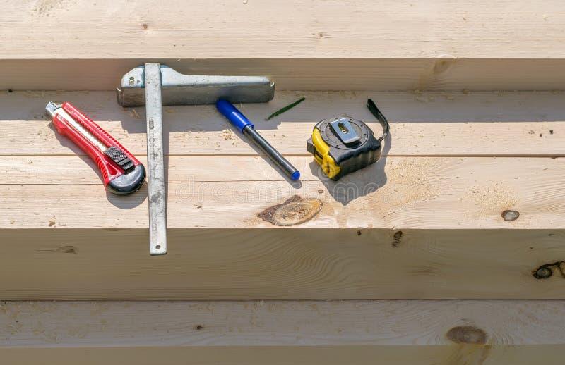 Machthaber, Maßband und Messer liegen auf dem Bauholz mit Sägemehl lizenzfreies stockbild