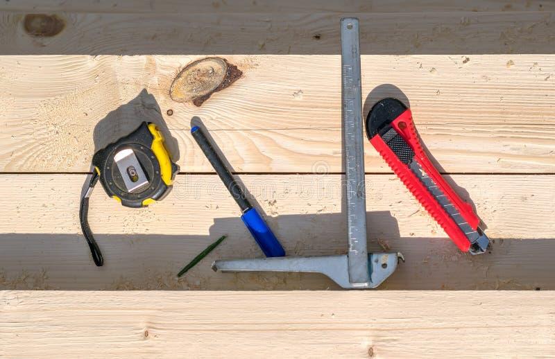 Machthaber, Maßband und Messer liegen auf dem Bauholz mit Sägemehl stockfotografie