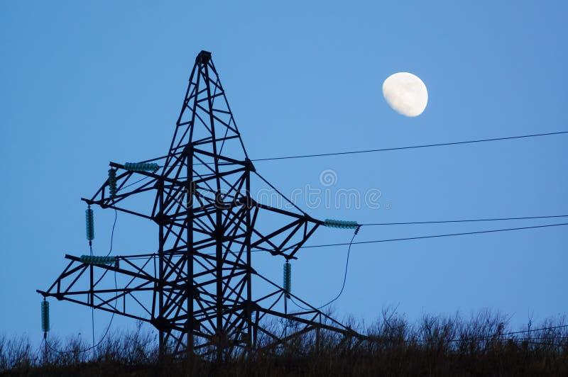 Machts pylon silhouet en maan stock foto