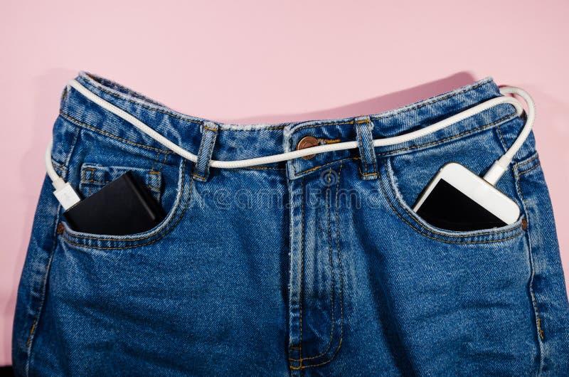 Machtsbank en een telefoon in jeans royalty-vrije stock foto's