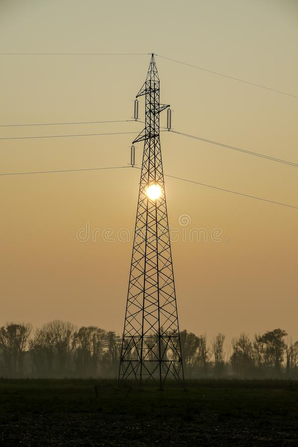 machtslijnen en elektriciteitspylonen bij zonsondergang, digitaal fotobeeld als achtergrond royalty-vrije stock foto's