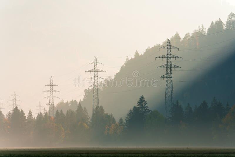 Machtslijnen en roosterkruisen op een wazige ochtend in een bergvallei met dalings rond kleur bos allen royalty-vrije stock afbeelding