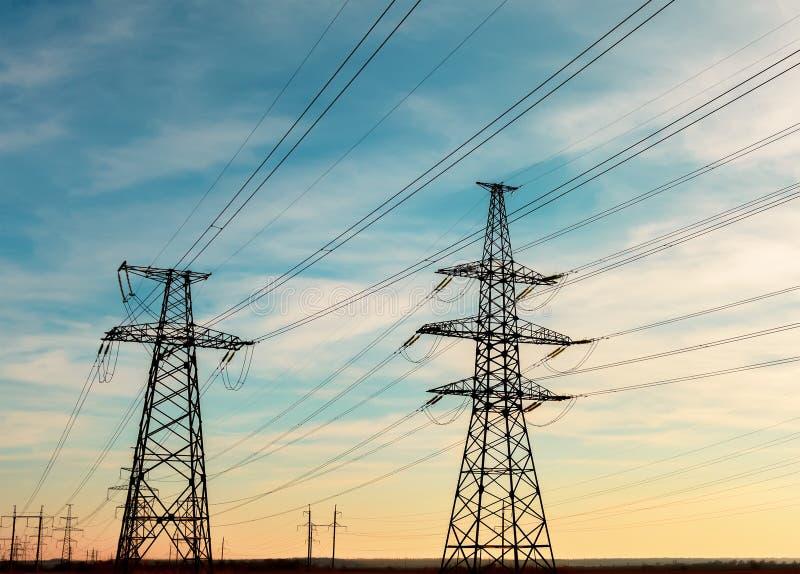 Machtslijnen met hoog voltage bij zonsondergang De post van de elektriciteitsdistributie Toren van de hoogspannings de Elektrisch royalty-vrije stock foto