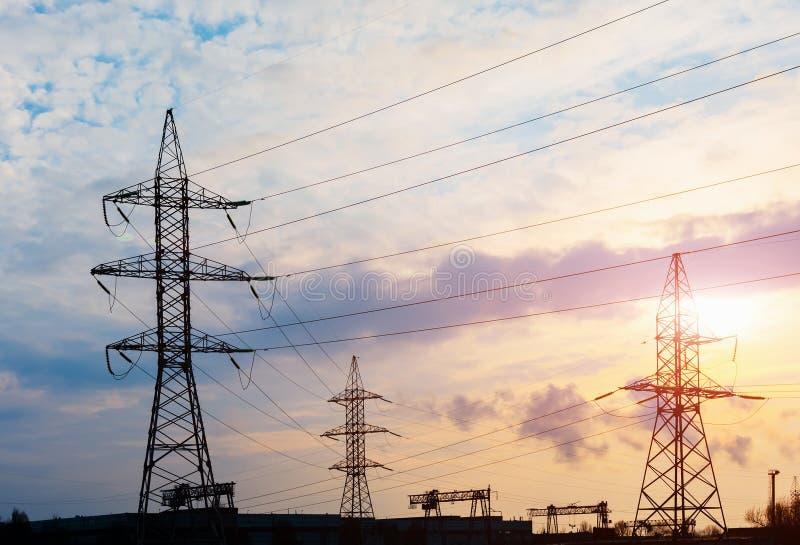 Machtslijnen met hoog voltage bij zonsondergang De post van de elektriciteitsdistributie Toren van de hoogspannings de Elektrisch royalty-vrije stock afbeelding