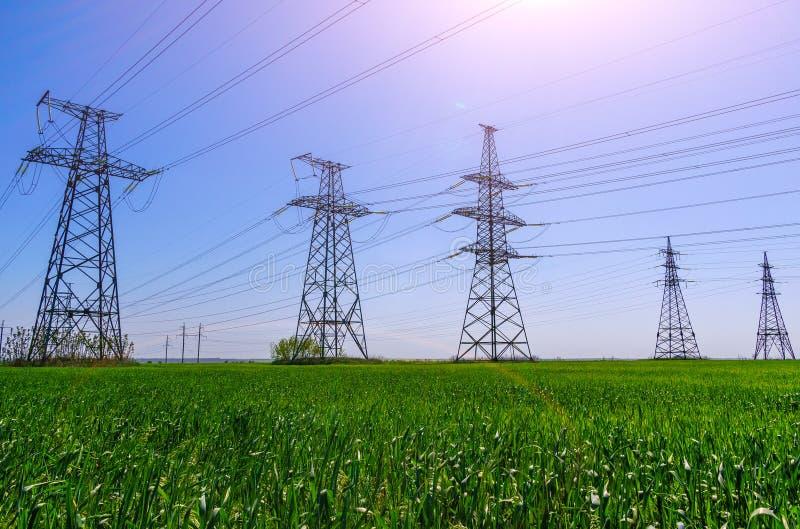 Machtslijnen met hoog voltage bij zonsondergang De post van de elektriciteitsdistributie royalty-vrije stock foto