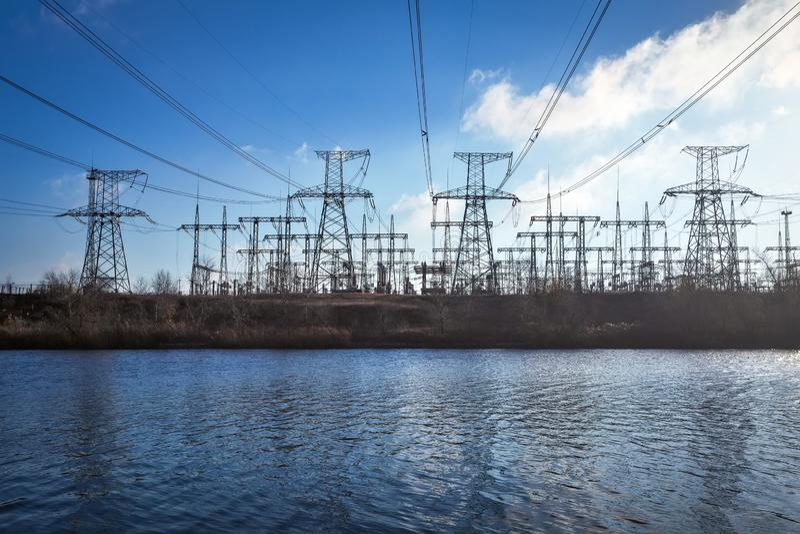 Machtslijnen met hoog voltage op de kust van meer royalty-vrije stock fotografie