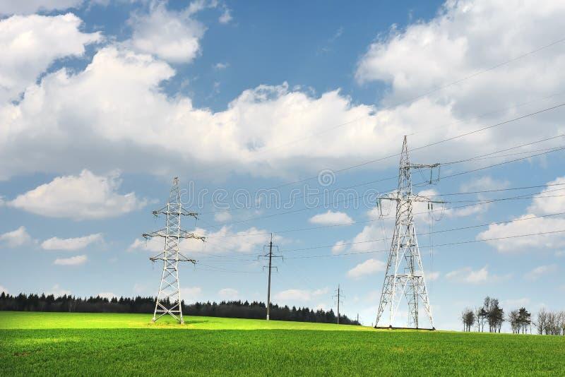 Machtslijnen met hoog voltage op groen gebied tegen blauwe hemel met witte wolken Machtslijn in groene weide stock fotografie