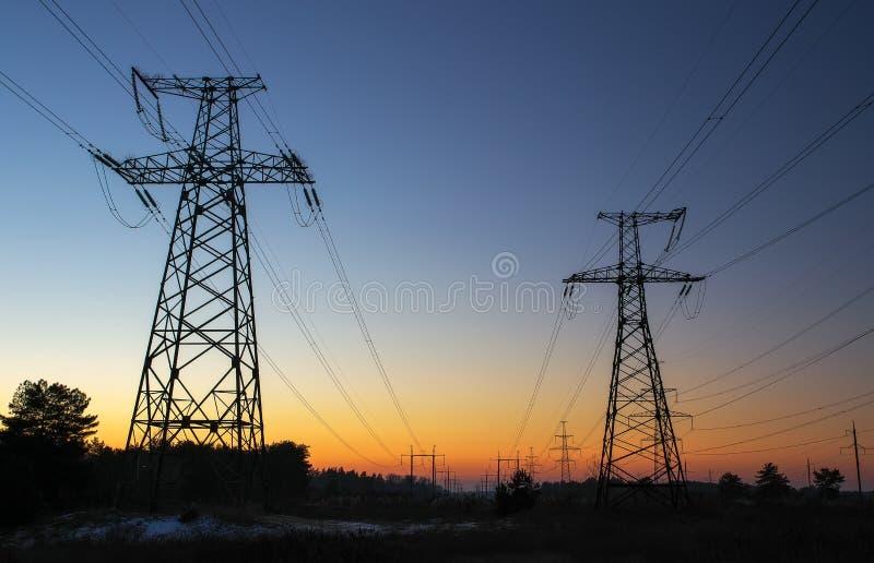 Machtslijnen met hoog voltage tijdens zonsopgang stock afbeeldingen