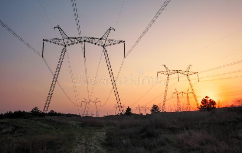 Machtslijnen met hoog voltage tijdens zonsopgang royalty-vrije stock afbeeldingen