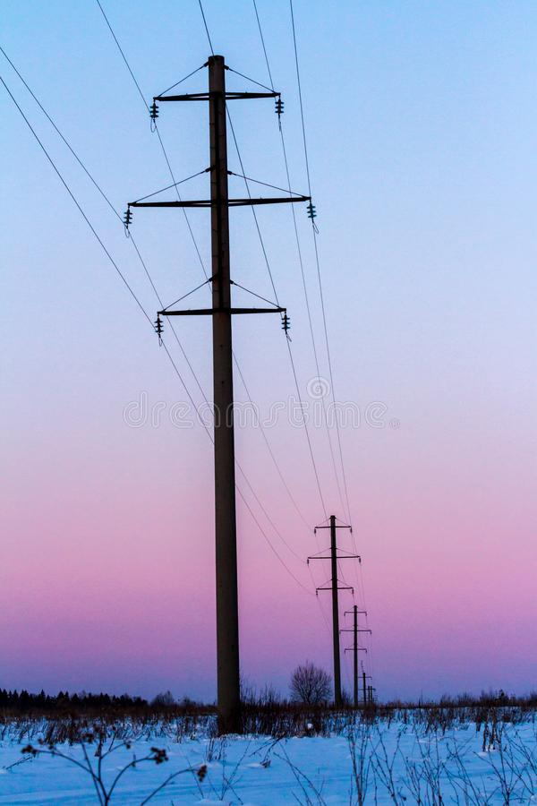 Machtslijnen op de winter sneeuwgebied bij zonsondergang Toren van de hoogspannings de Elektrische Transmissie Het landschap van  royalty-vrije stock afbeelding