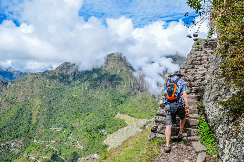 MACHU PICCHU, CUSCO, PERU- JUNE 4, 2013: Tourist climbing Huayna Picchu mountain for the best panoramic view of Machu Picchu stock image