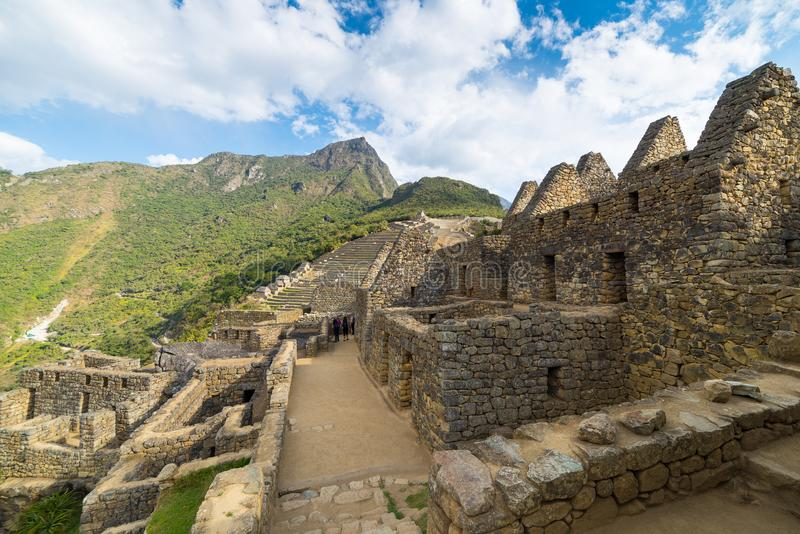 Machu Picchu illuminated by the last sunlight. Wide angle view from below over the glowing terraces with scenic sky. Machu Picchu royalty free stock images