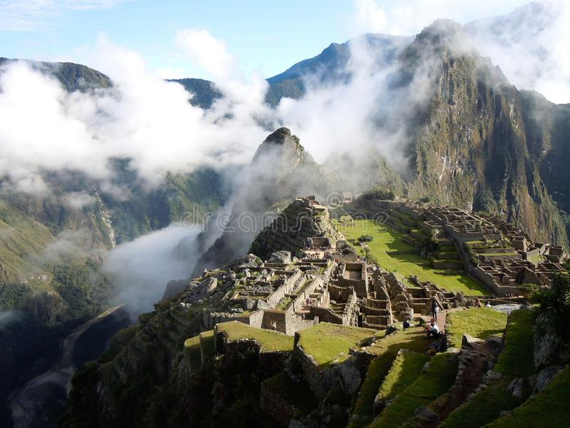 Machu Picchu on mountain top surrounded by clouds above, around and below in deep valley. Machu Picchu at mountain summit surrounded by clouds with deep valley stock images