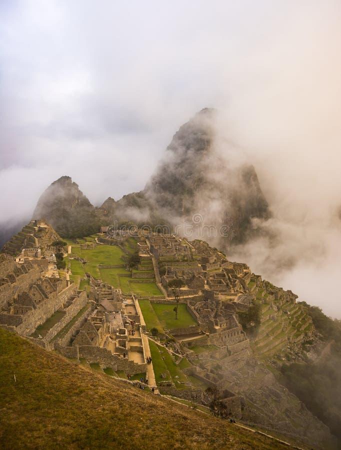 Machu Picchu som är upplyst vid det första solljuset som är kommande från öppningen, fördunklar ut Staden för Inca` s är den mest royaltyfria bilder