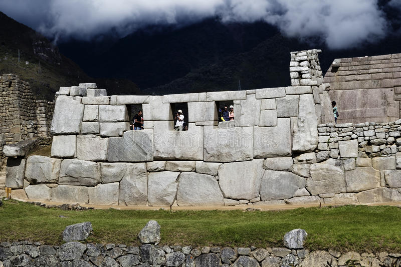 Machu Picchu Three Windows With Tourists And Clouds stock photography