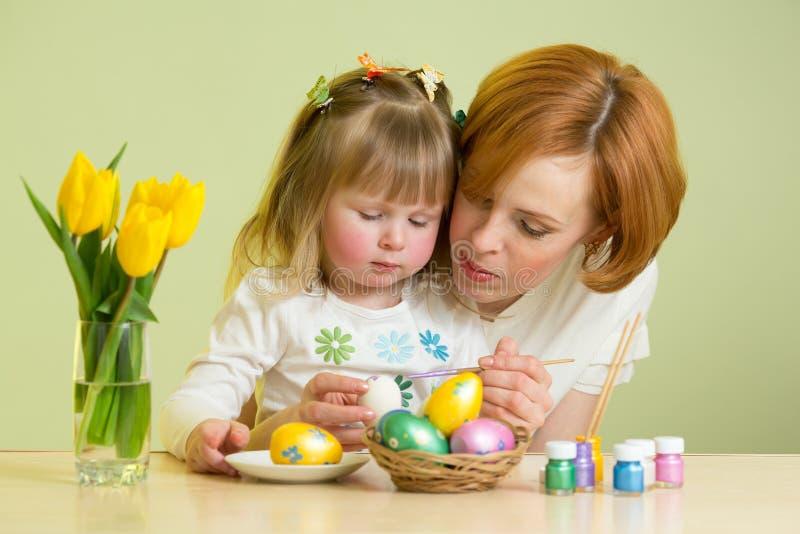Macierzyści i dzieciak dziewczyny farby Wielkanocni jajka zdjęcia stock
