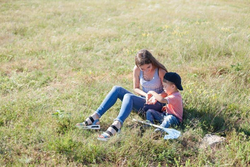 Macierzyści i młodzi syna chwyta insektów motyle fotografia stock