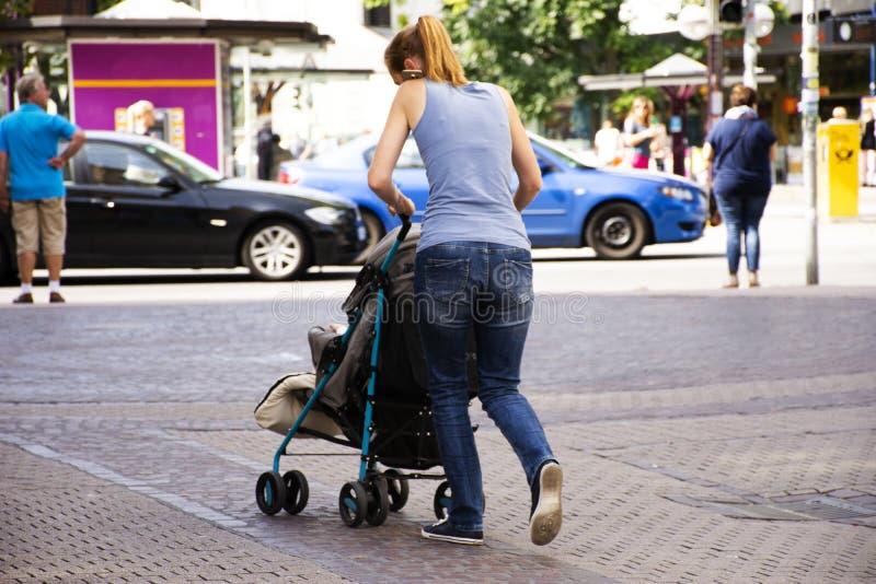 Macierzyści niemieccy ludzie pchają spacerowicza fracht z dzieckiem i opowiadać telefonem komórkowym na footpath w Heidelberg, Ni obrazy royalty free