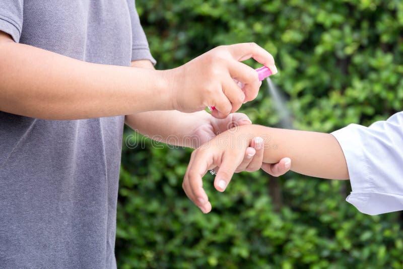 Macierzyści opryskiwanie insekta repellents na jej syn ręce zdjęcie stock