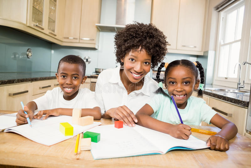Macierzyści pomaga dzieci robią ich pracie domowej obraz royalty free