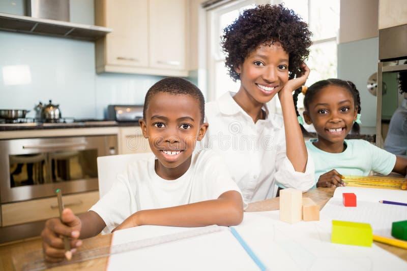 Macierzyści pomaga dzieci robią ich pracie domowej obraz stock