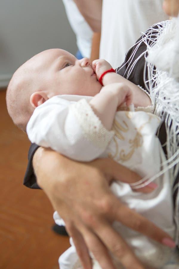 Macierzysta caucasian młoda kobieta trzyma małego dziecięcego dzieciaka w bapt zdjęcie stock