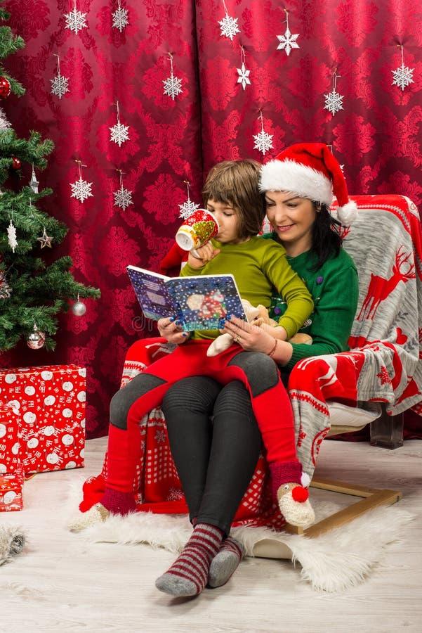 Macierzysta czytelnicza Bożenarodzeniowa książka jej dzieciak zdjęcie stock