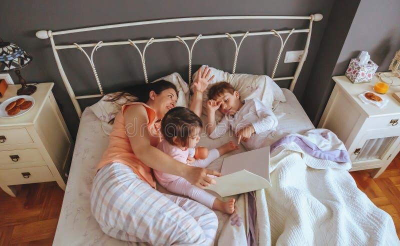 Macierzysta czytelnicza książka jej synowie w łóżku fotografia royalty free