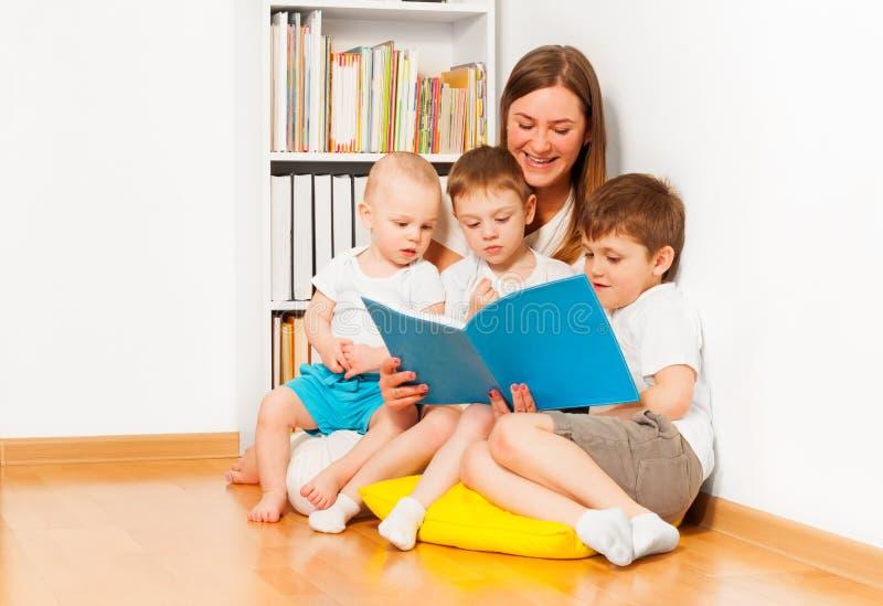 Macierzysta czytelnicza książka jej trzy różnorodnego dzieciaka zdjęcia stock