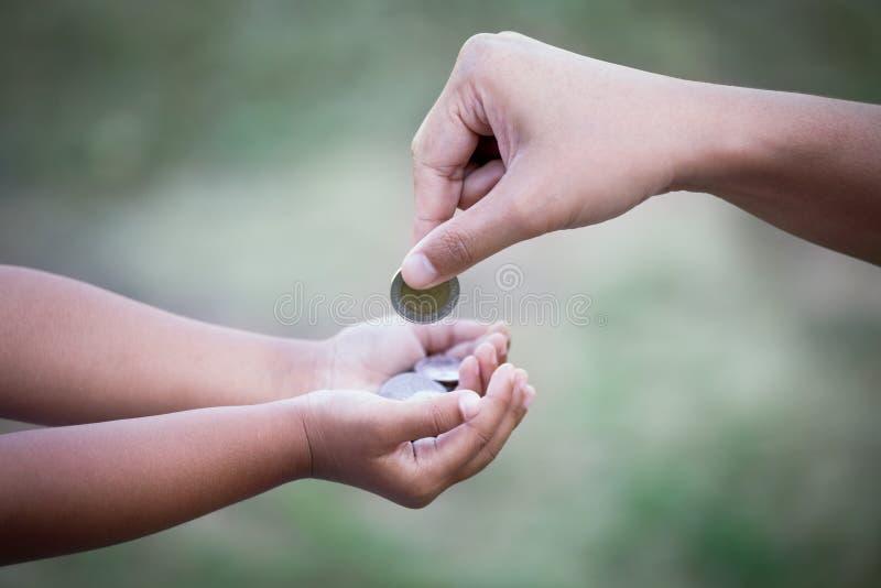 Macierzysta daje moneta dziecko jako oszczędzanie pieniądze pojęcie obraz royalty free