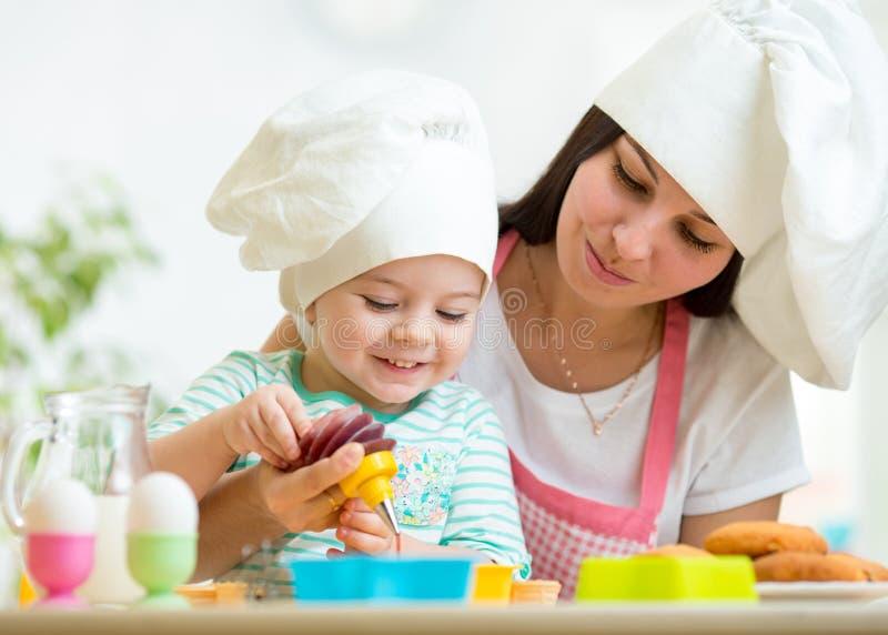 Macierzysta i dzieciak dziewczyna robi ciastkom zdjęcia royalty free